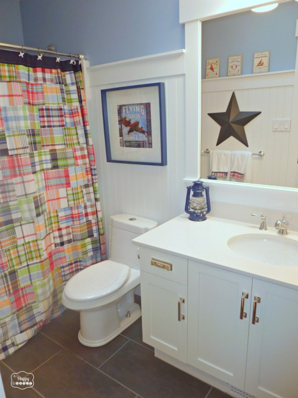 Plaid shower curtain and star picture in a blue and white bathroom.