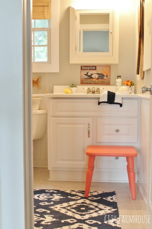 Blue and white rug with orange stool in a neutral bathroom.