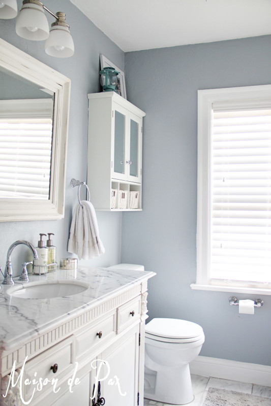 Soft blue walls in a all white bathroom.
