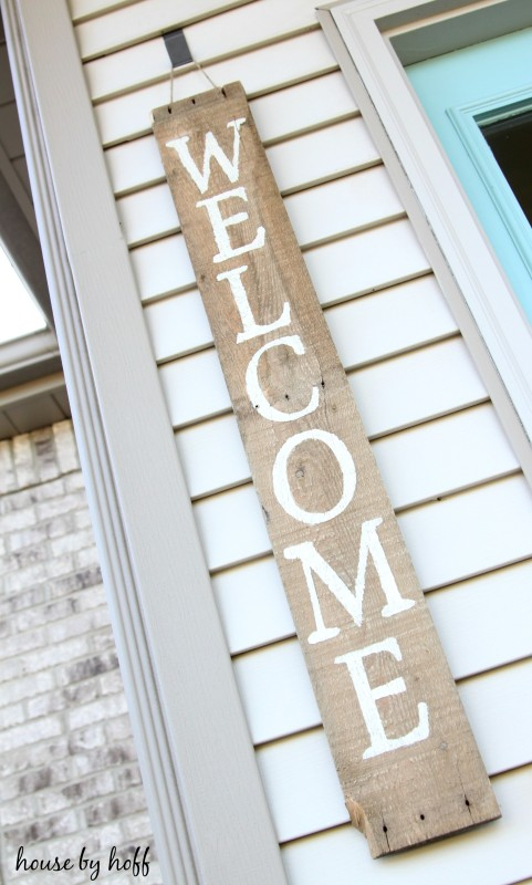 The word welcome on a wooden sign hanging by the doorway.