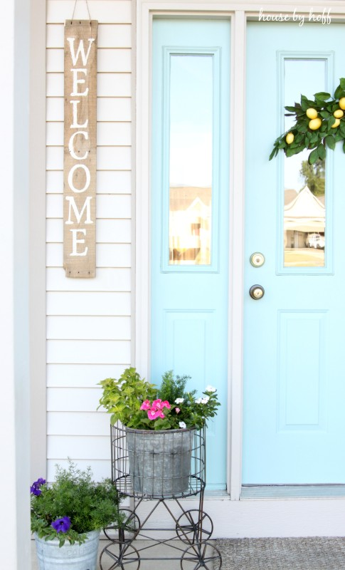 Light blue door, and flowers plus the welcome sign hanging outside.
