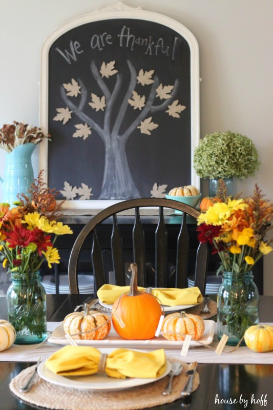 Chalkboard in dining room with we are thankful written on it with a tree and leaves on it to.