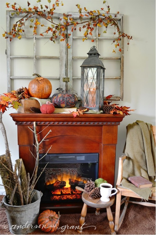 Fireplace that is on with pumpkins and lanterns on mantel.