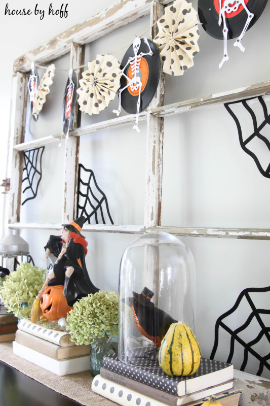 Halloween garland hanging up and witches in cloches.