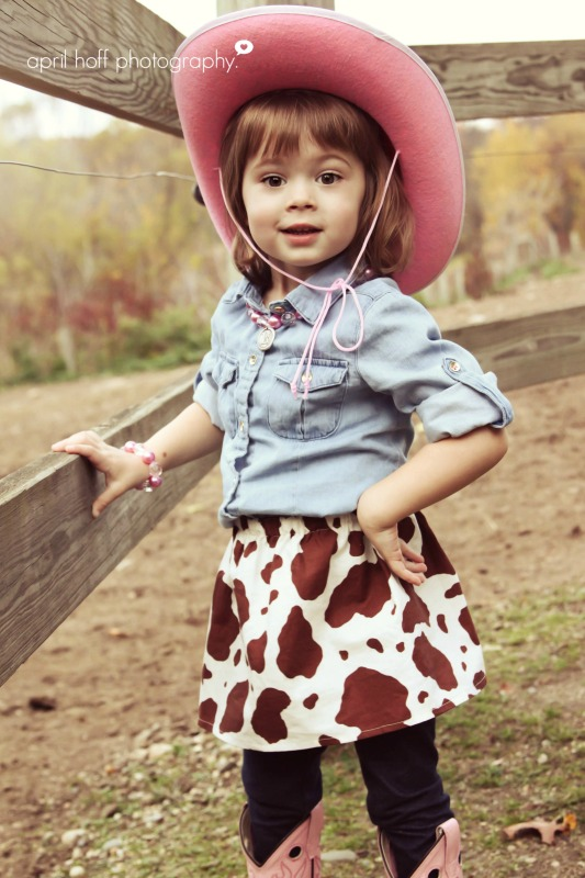 Little girl with a pink cowboy hat and cowgirl skirt on in picture.