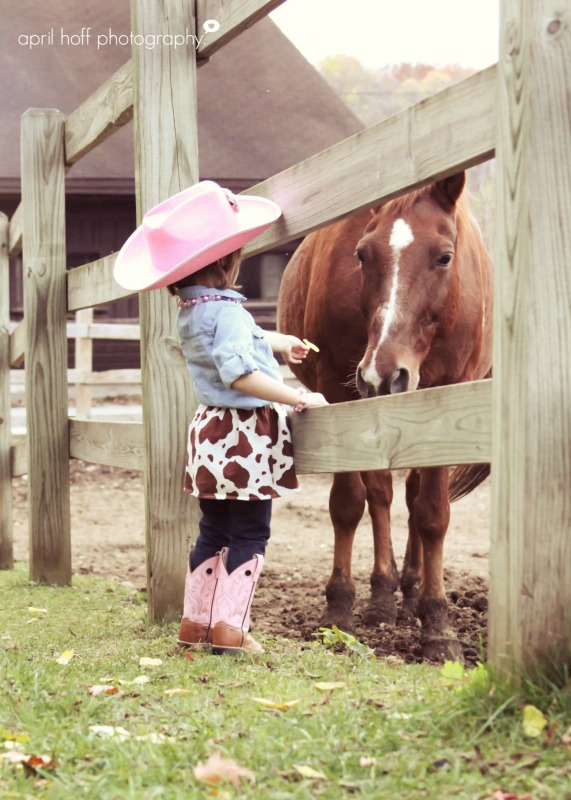Girl petting a horse in her cowboy boots by a fence.