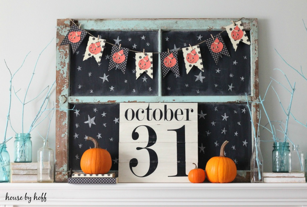 Sign saying October 31 and pumpkins on mantel.