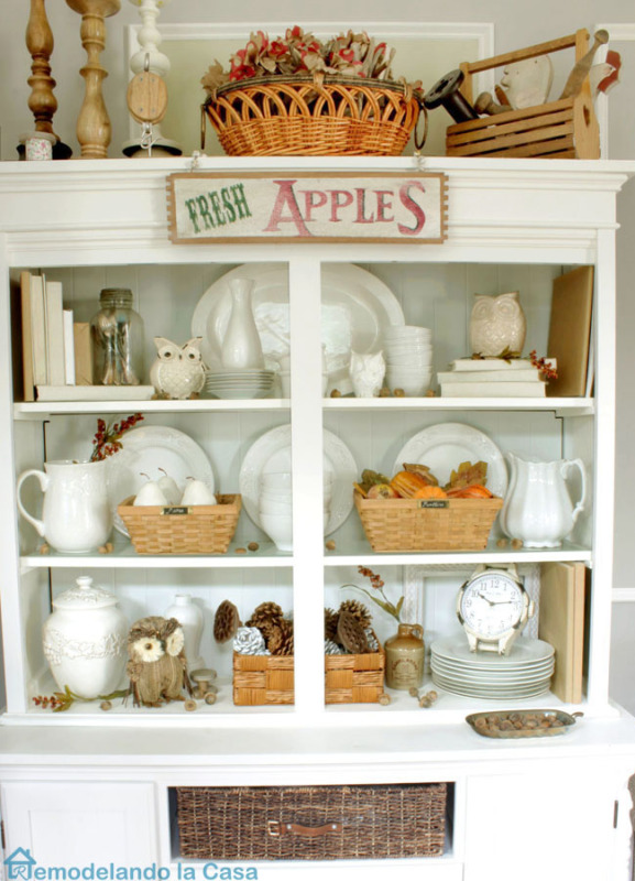 White hutch decorated for fall with red and orange and green.