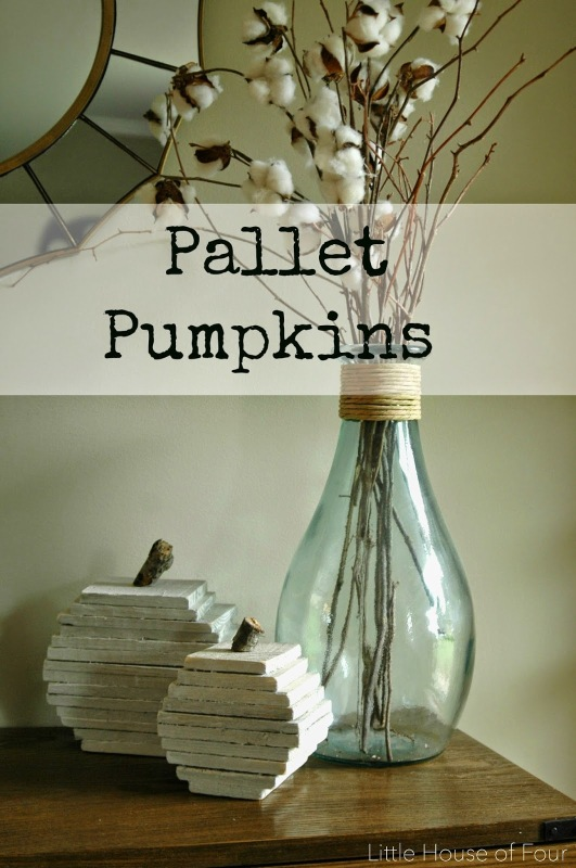 Desk with pallet pumpkins and a clear vase with twigs.