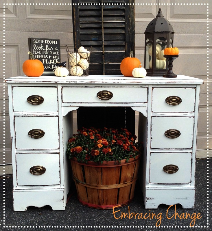 White distressed desk with orange pumpkins on it.