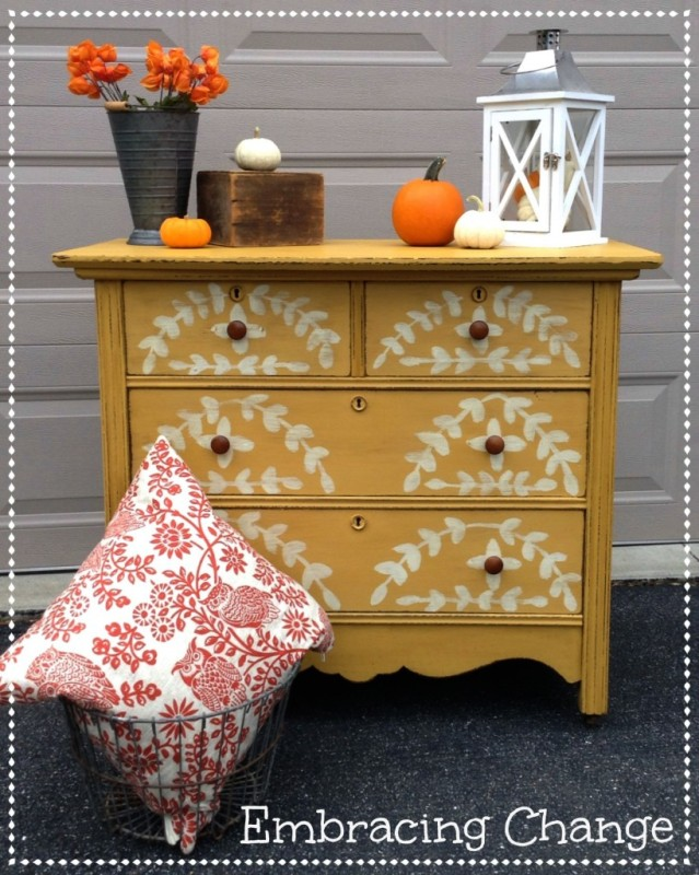 Mustard yellow dresser with pumpkins on top.