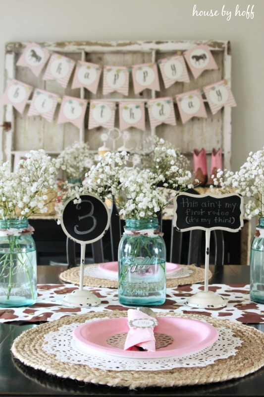 Table setting with pink plates and mason jars filled with white flowers on table.