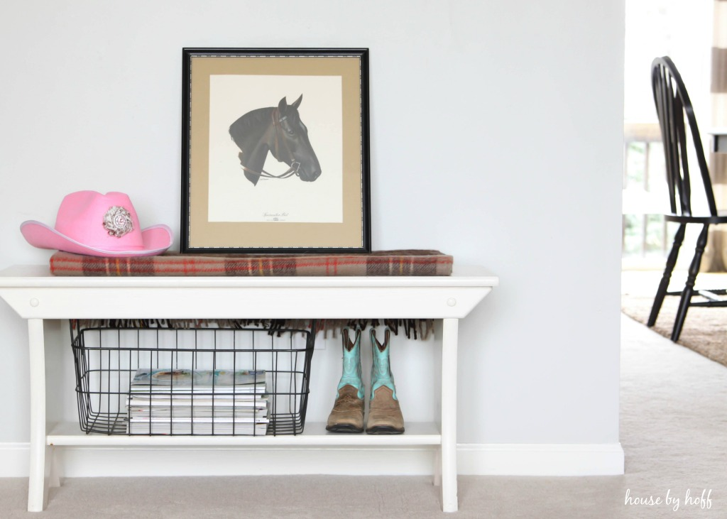 Pink cowboy hat and horse framed picture on table.