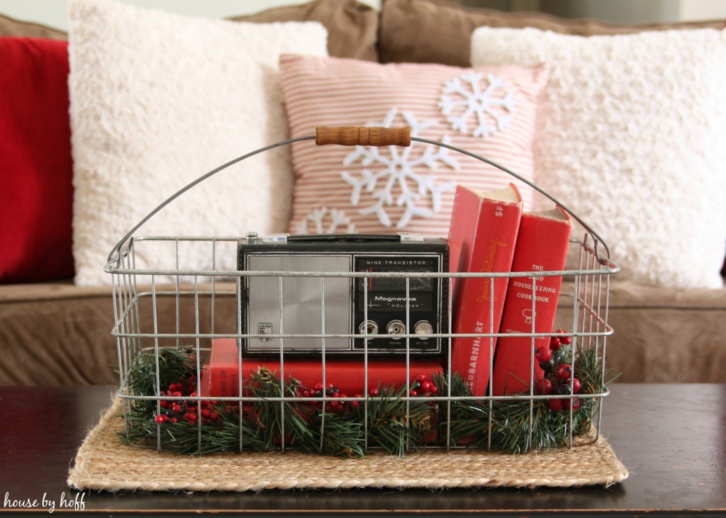 A wire basket with a small vintage radio, old books and holly.