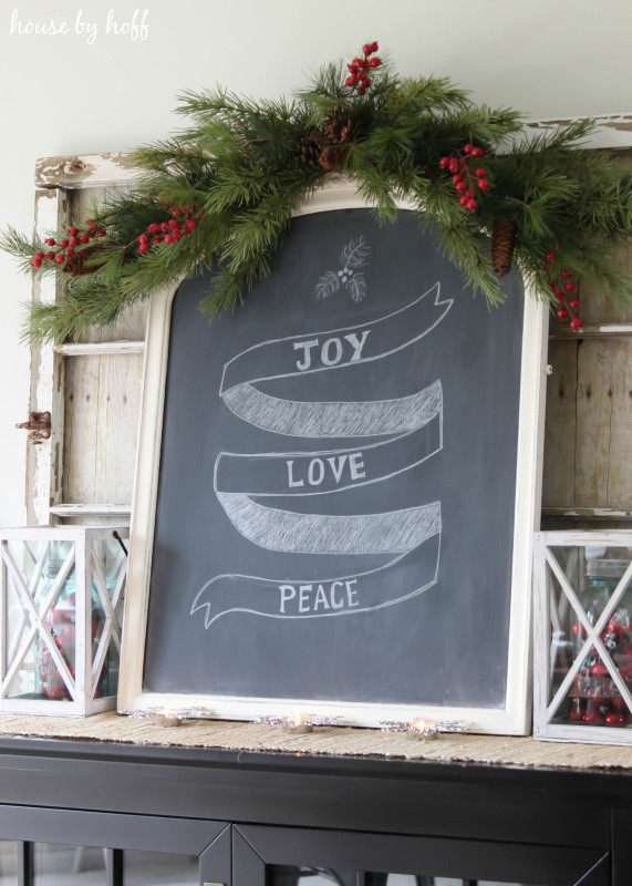 A chalkboard with Joy Love and Peace written on it, plus a garland of holly on the top of the board.
