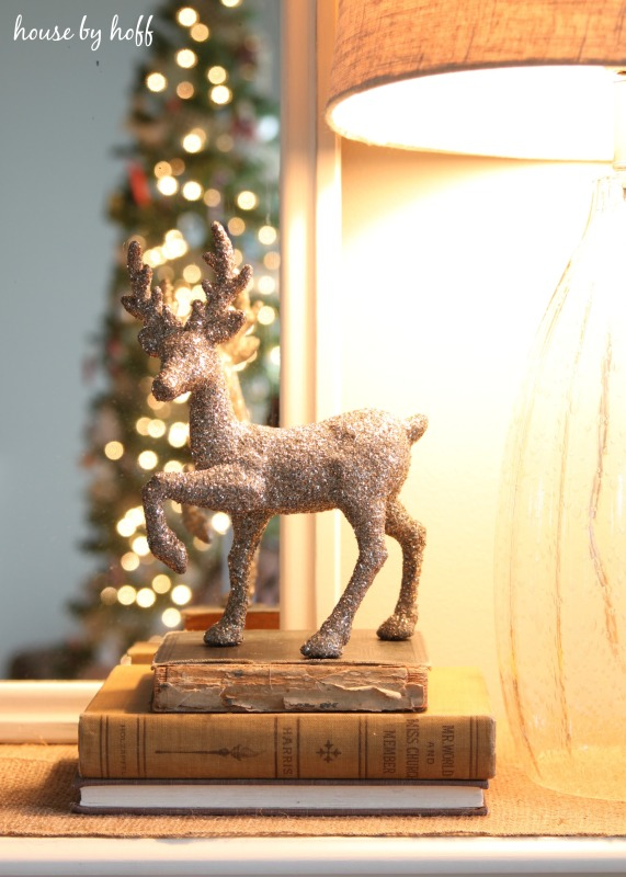 Up close of the sparkly deer figurine on top of old books.