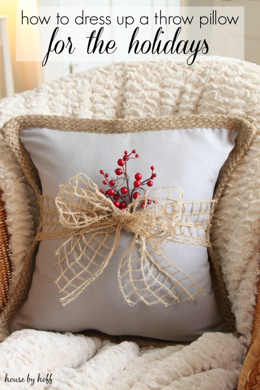 A cozy armchair with a pillow that has a bow and some red berries around it.