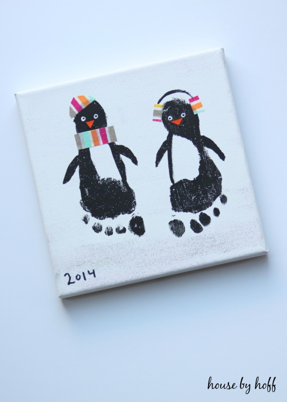 Two penguins with multicoloured hats and scarves on.