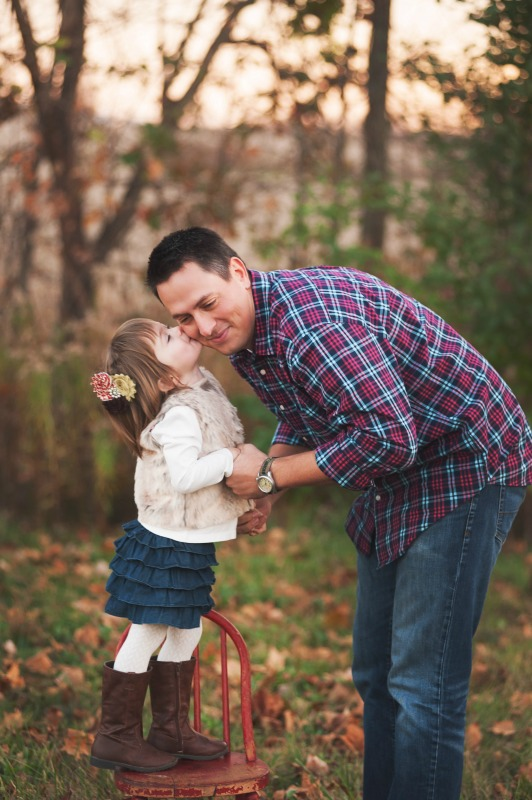 Little girl standing on a chair kissing Dad's cheek.