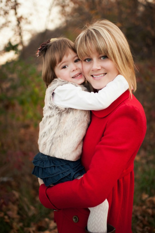 A blonde Mom holding her daughter with her arms wrapped around Mom's neck.