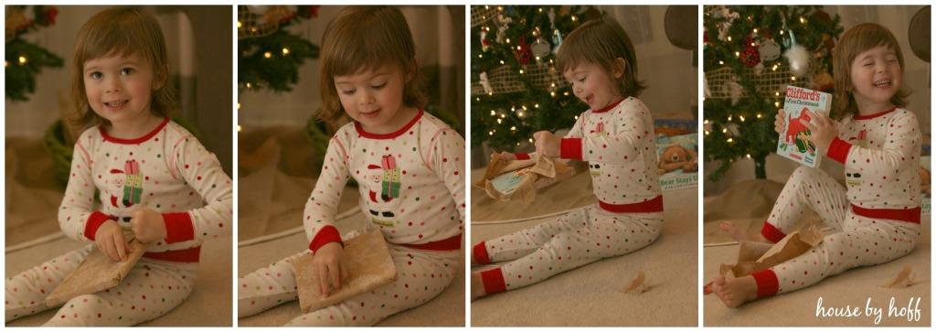 A little girl opening up a Christmas book with delight.