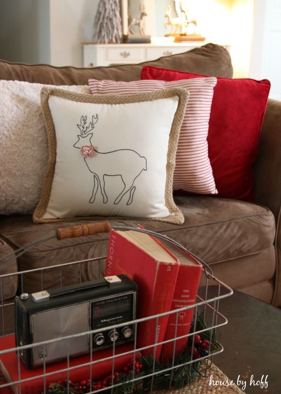 DIY Stenciled Reindeer Pillow on the couch with other pillows.