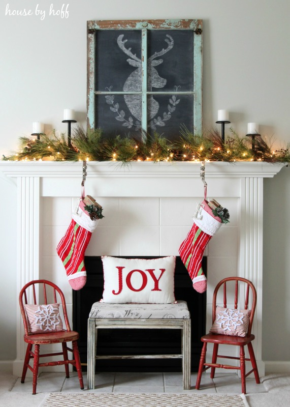 A white fireplace with two stockings hanging and two chairs in front of it, there a chalkboard with a deer drawn on it on the mantel.