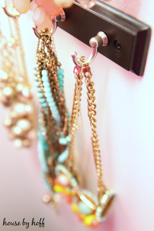 Gold chains hanging on metal hooks.