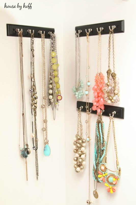 Multi colored necklaces hanging on hooks on the wall.