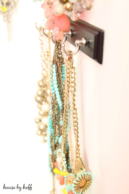 Side view of necklaces hanging on hooks.