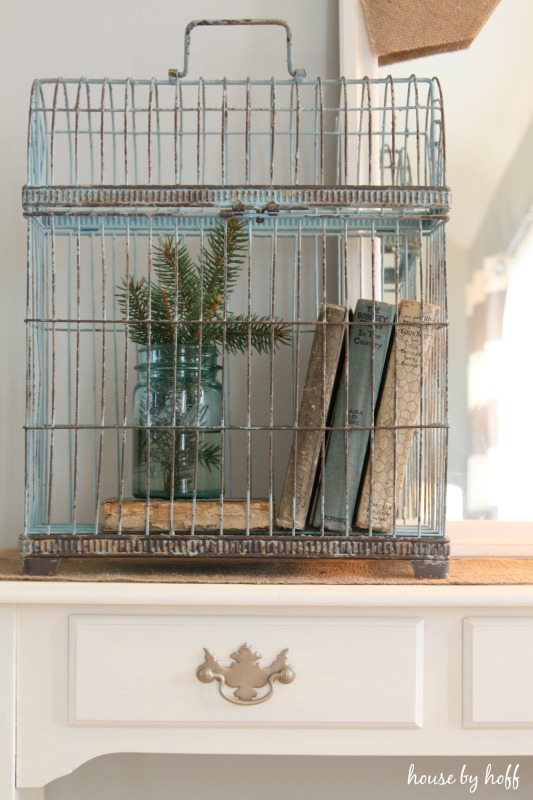 A birdcage filled with antique books, and evergreen clippings.