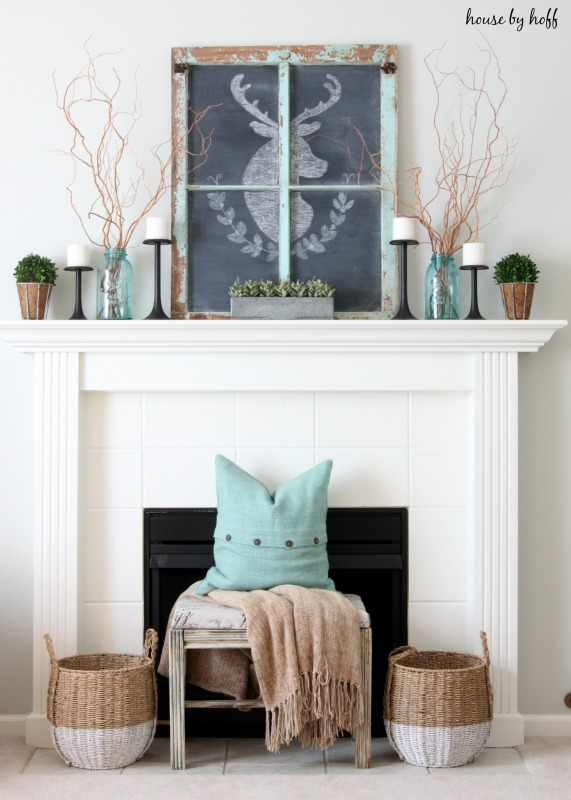 A white fireplace with a bench in front of it, a blue pillow on the bench and a chalkboard deer on top of the mantel.