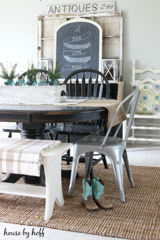 A dining room table with cowboy boots beside it.