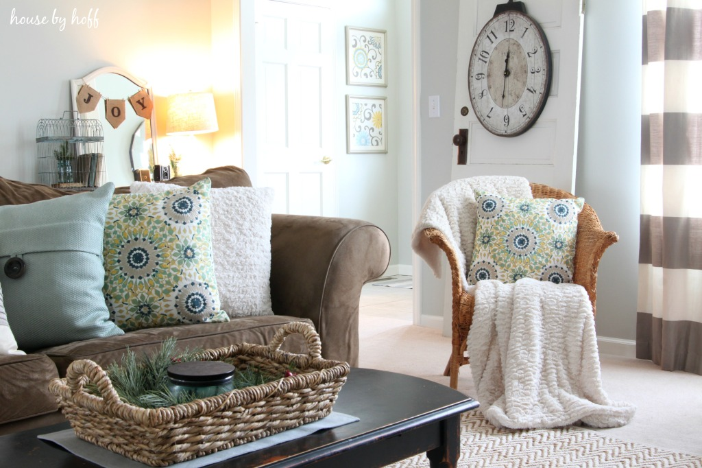 A brown couch, wicker chair both with floral pillows on it.