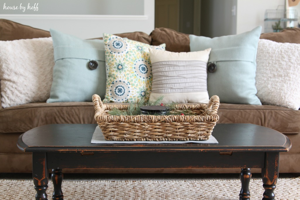 A dark wood coffee table with a wicker basket on top of it.