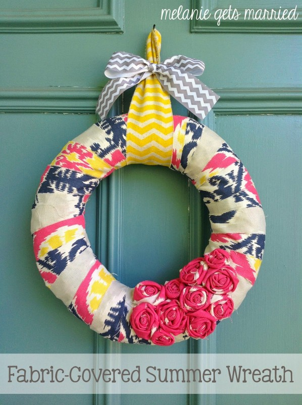 A wreath that is covered in fabric with tones of pink, yellow and grey.