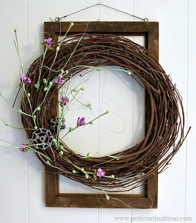A grapevine wreath with small purple flowers.