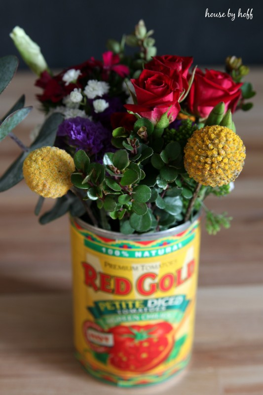 A tomato tin can filled with red, yellow and purple flowers.