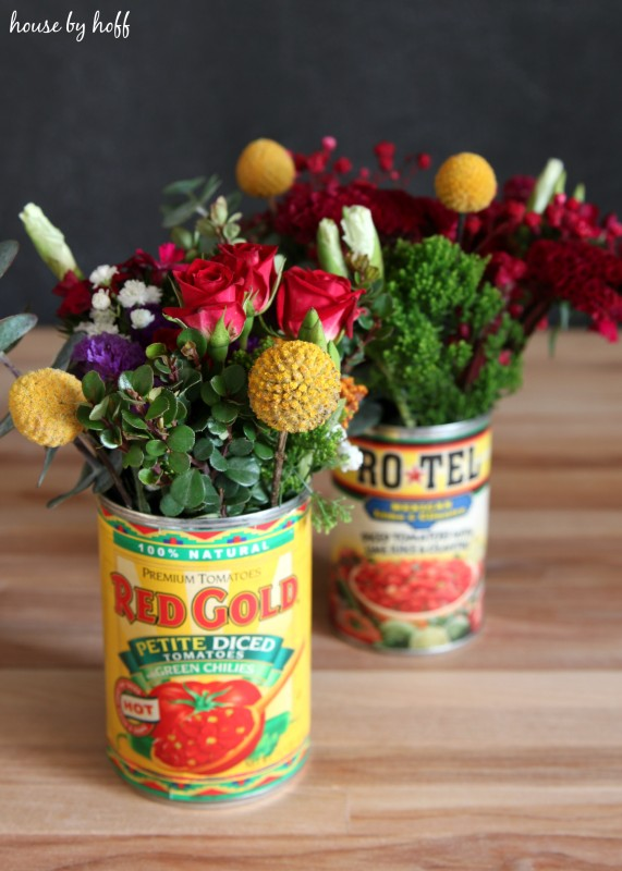 Two tin cans filled with flowers.