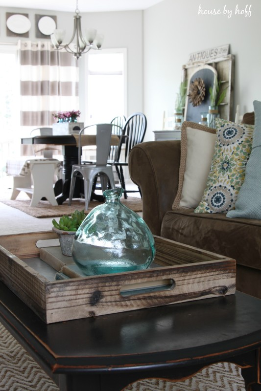 Coffee table in living room with glass jar on it.