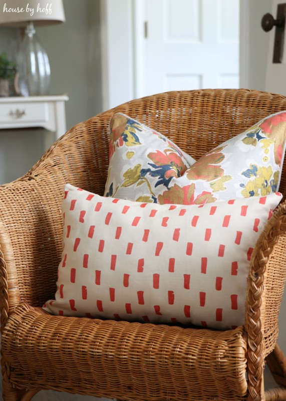 Red and white throw pillow and a flower pillow on a wicker chair.