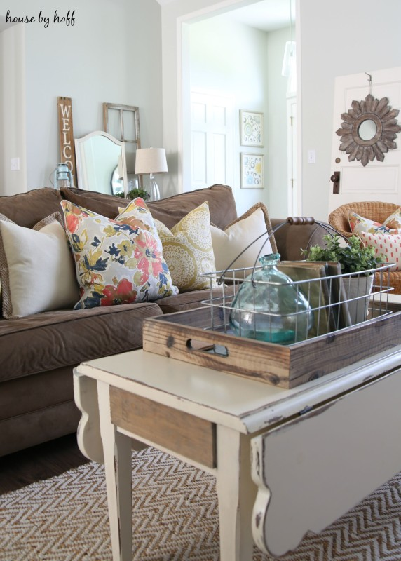White coffee table in the living room with brown couch and throw pillows.
