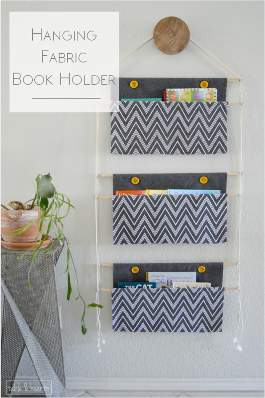 A fabric book holder hanging on a wall.