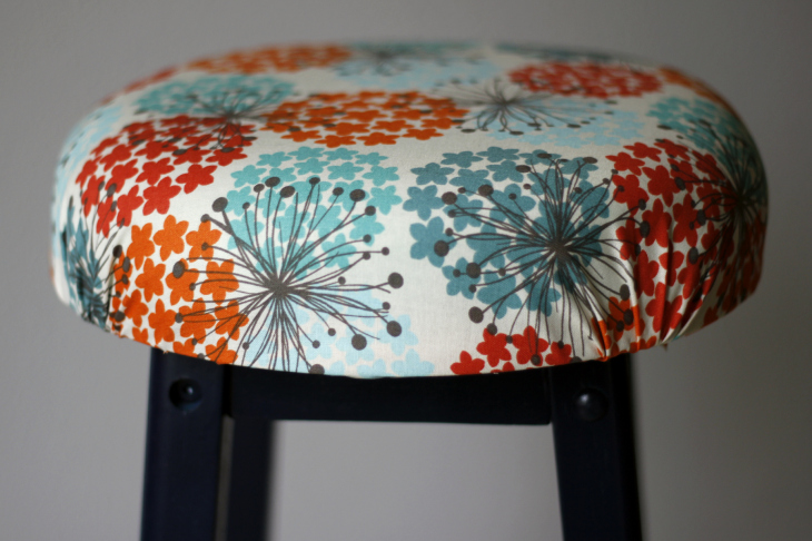 Blue, orange, red, floral fabric on top of black stool.