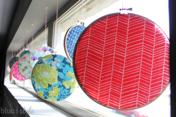 Red, blue and floral circle fabric art hanging in window.