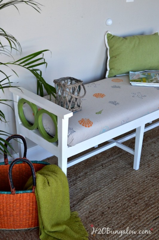 Outdoor bench with a green and white and seashell cushion.