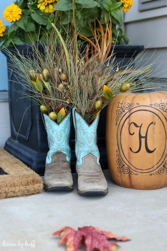 Cowboy boots filled with wheat grass on the front porch.