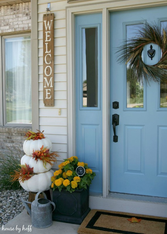 White stacked pumpkins, yellow flowers and a watering can on the front stoop.