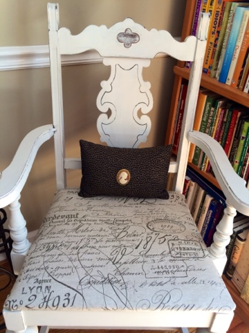 White chair with French vintage pillow cushion.