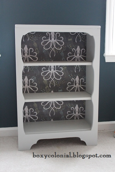 Bookshelf with black and white fabric on the backside.